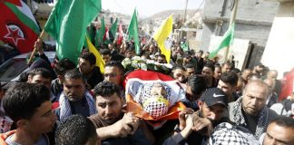 The body of Hamdi Nassan from the village of al-Mughayir, who was shot dead by Israeli settlers, is carried to his last resting place