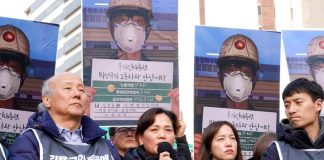 Kim's mother speaking at a rally in front of pictures of her son taken just before his death at work