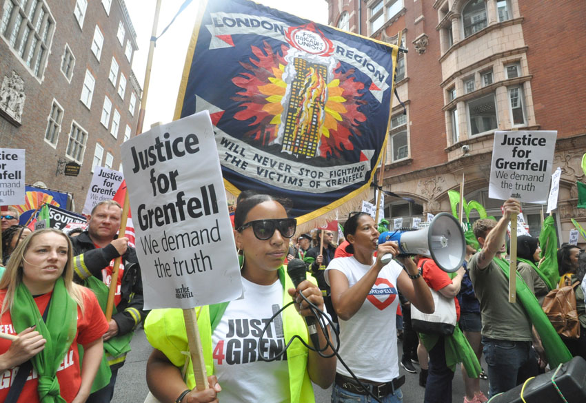 Firefighters march with survivors and local residents on the first anniversary of the Grenfell inferno