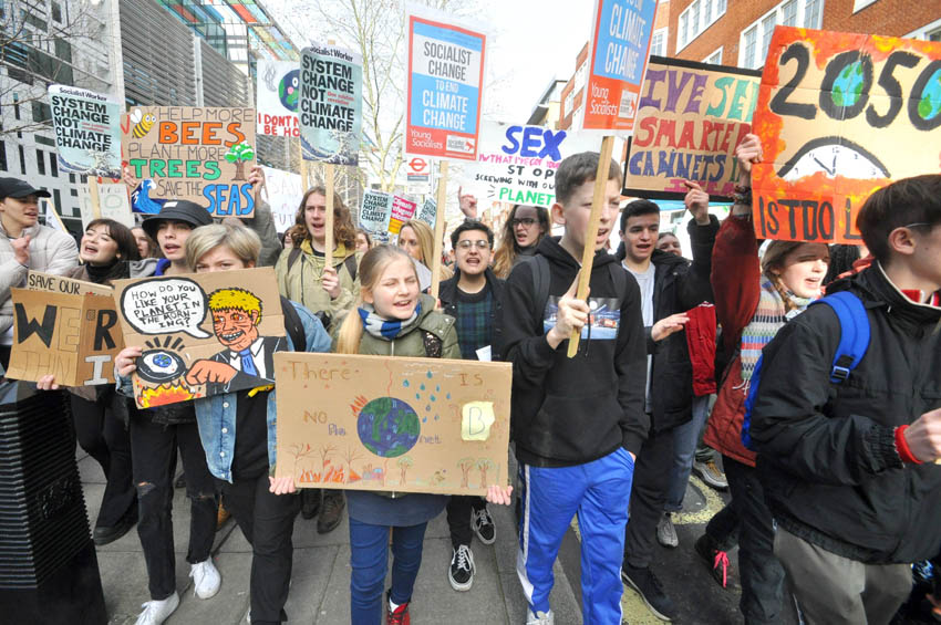 School youth at the front of a 1,000-strong march around Westminster, London, England demanding an end to capitalism