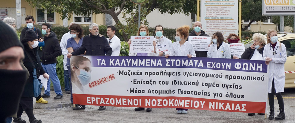Doctors and nurses demonstrate at the Nikes General Hospital, Piraeus, Greece, yesterday morning against Greek government policies. Banner slogans demand mass employment of health staff, requisition of the health private sector, protection for all