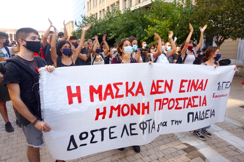Greek school students march with a banner stating: 'Masks are not the only protection – give money for education'