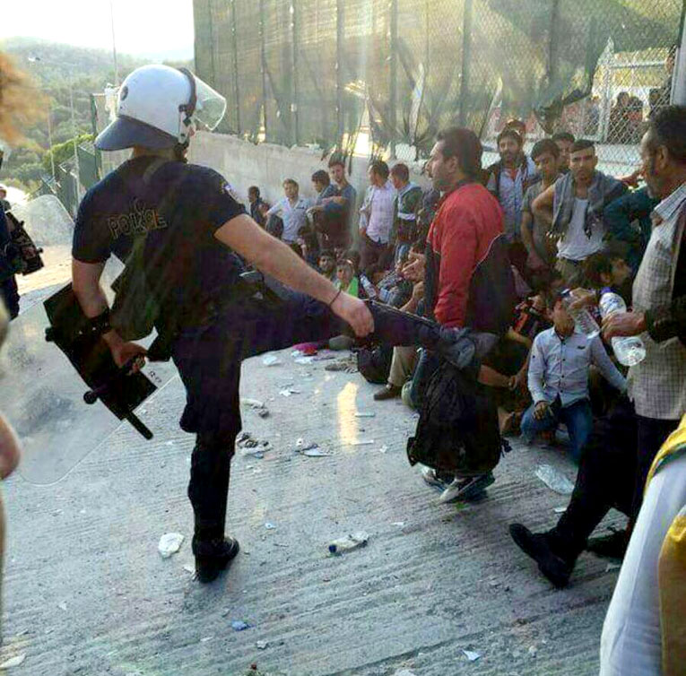 Greek policeman kicks out at refugees in the Moria camp in Lesbos